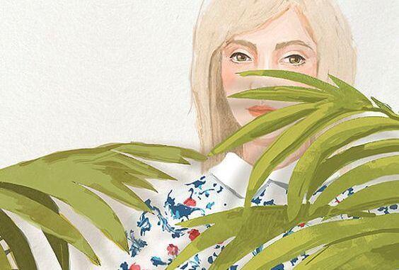 Kvinde gemmer sig bag ved plante i frygt for kritik