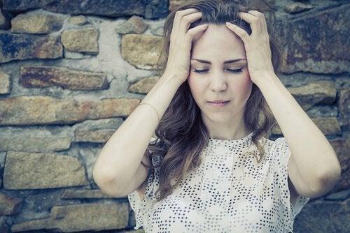 Kvinde tager sig til hoved i frygt for at blive såret