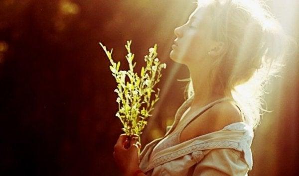 Kvinde står i solen med blomst