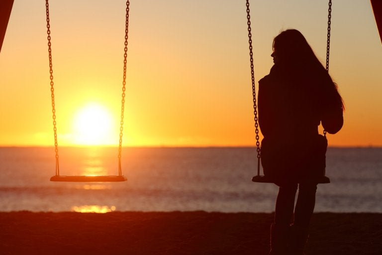 Kvinde sidder alene på gynge og ser solnedgangen