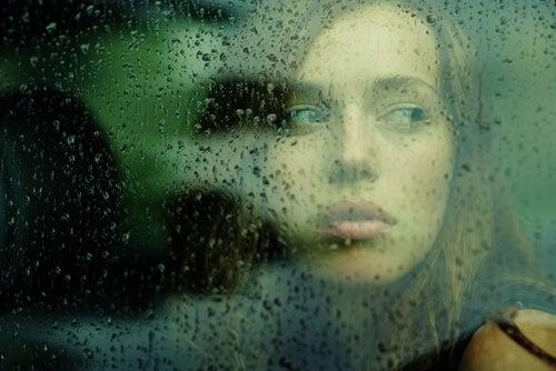 trist kvinde ser ud af vindue. At værdsætte livet
