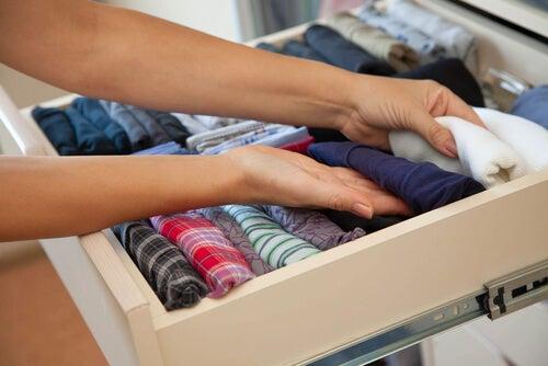 Kvinde organiserer skuffe med tøj