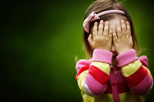 Pige gemmer sit ansigt bag sine hænder