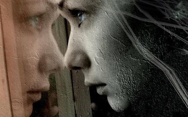 Trist pige ser ud af vindue og er berørt af mange spor og ar fra andre mennesker