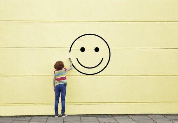 Person tegner smiley på væg