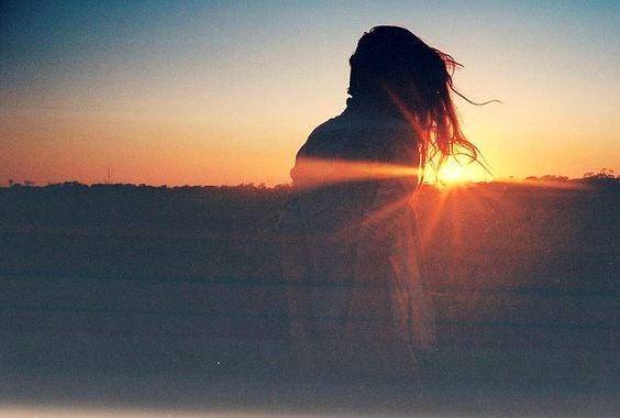 Pige foran solnedgang