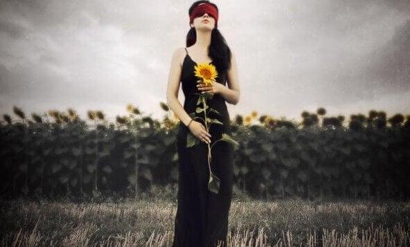 Kvinde med bind for øjnene står med solsikke