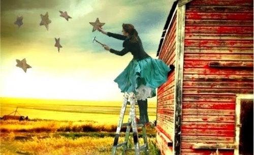 Kvinde maler stjerner på himmel