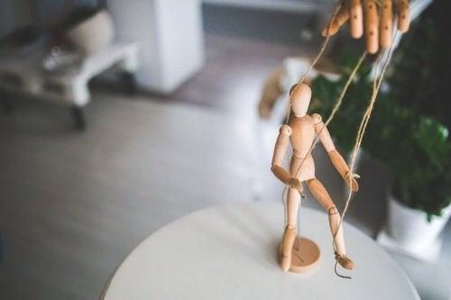 Træmand føres af snore som symbol på følelsesmæssig manipulation