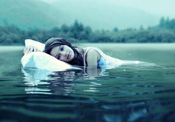 Kvinde flyder i vand med pude