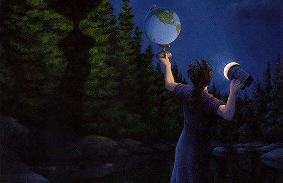 Person lyser på globus