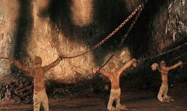 Mænd sidder lænket i Platons grotte