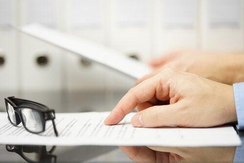 Mand ved skrivebord med papir er ved at snakke om chikane på arbejdspladen