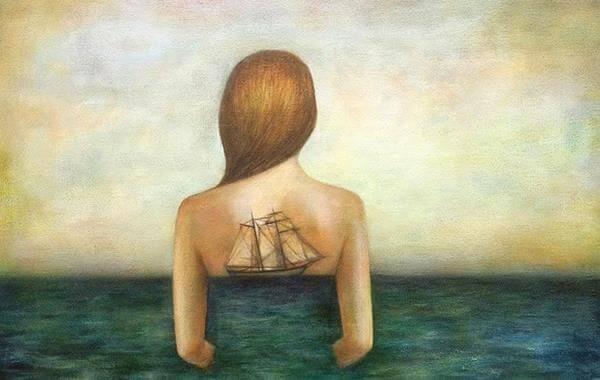 Kvinde i hav med båd på ryg