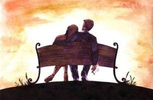 Et par sidder på bænk og er romantiske