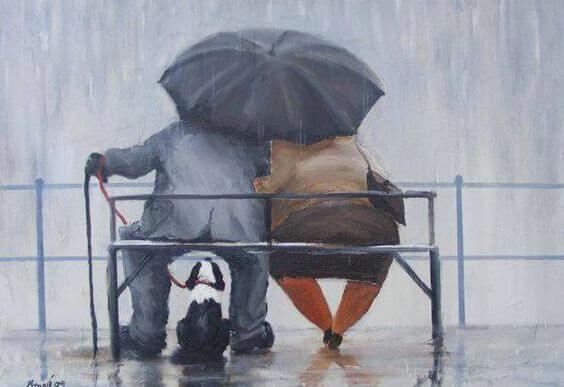 Ældre par sidder på bænk i regnvejr med paraply