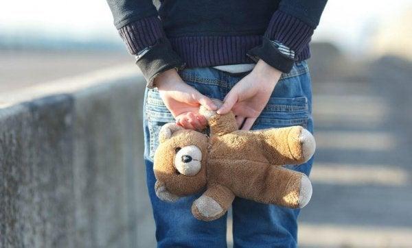 Barn står med bamse bag ryggen