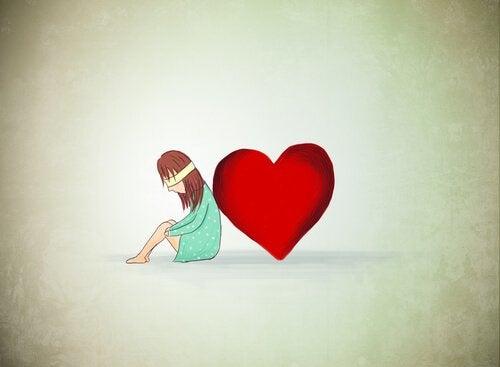 Pige med bind for øjnene sidder op af hjerte og oplever blind kærlighed