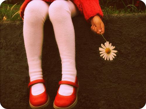 Barn sidder med blomst