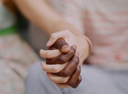 Par holder i hånd og viser kærtegn