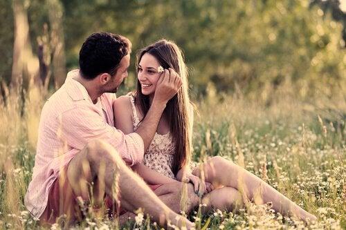 Forelsket par sidder på eng og nyder sensommer kærlighed