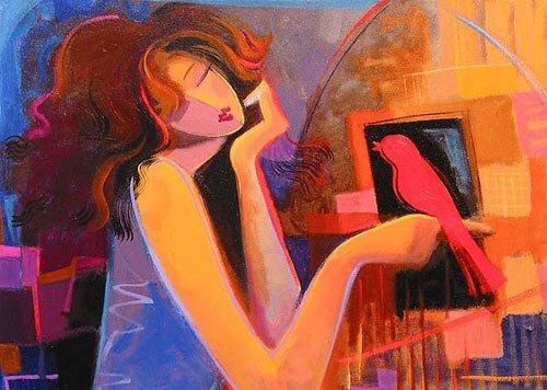 Kvinde sidder med fugl på fingeren