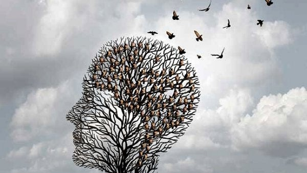 Fugle flyver væk fra træ formet som hoved som symbol for alzheimers
