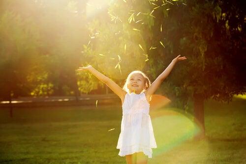 Et venligt barn med armene over hovedet kaster med blade