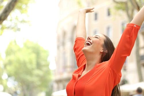Glad kvinder med hænderne over hovedet nyder fordele ved at gå ture