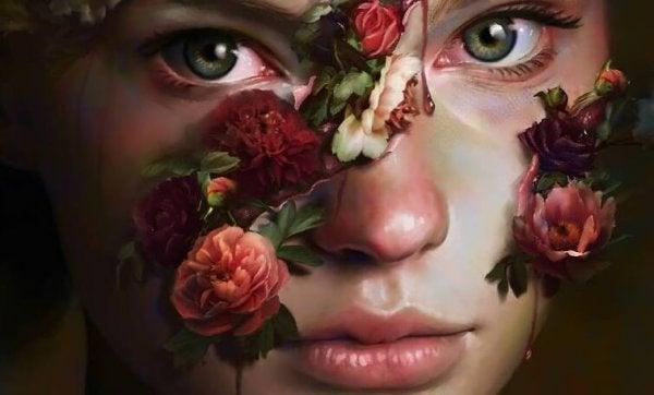 Nærbillede af god pige med blomster foran ansigtet