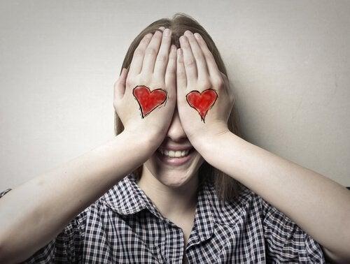 Kvinde med hænder for øjnene og hjerter tegnet på hænder oplever blind kærlighed