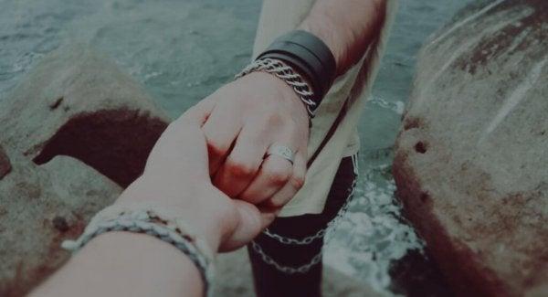 Personer holder i hånd foran hav