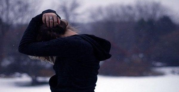 Kvinde står med hoved bøjet og hænderne over hovedet, da hun er træt af at lide af borderline personlighedsforstyrrelse