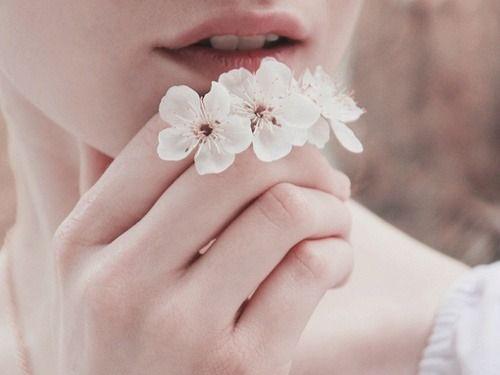 Hvide blomster foran mund på kvinde, der er minimalist og værdsætter de små ting