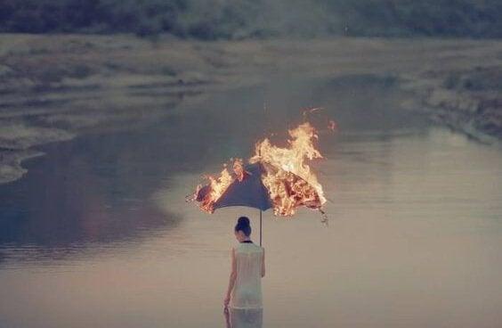 Kvinde står foran sø med brændende paraply