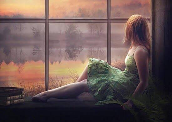 Kvinde sidder i vindue og er ved at tage en beslutning