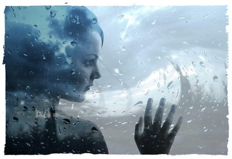 Kvinde rører ved vådt vindue