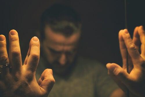 Trist mand med hænder på spejl ønsker at tage benzodiazepiner