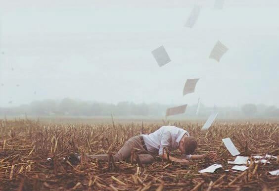 Mand på mark med papirer flyvende omkring sig