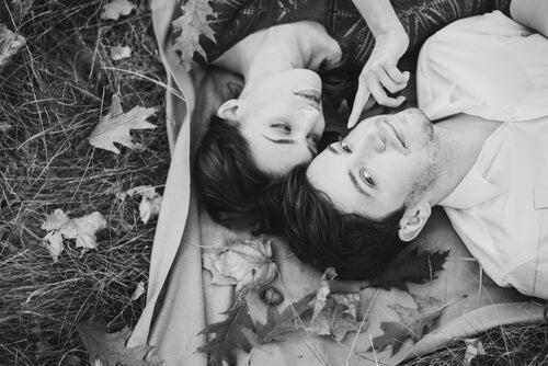 Par ligger på græs og er romantiske