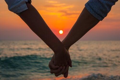 Par holder i hånd ved solnedgang og nyder sensommer kærlighed