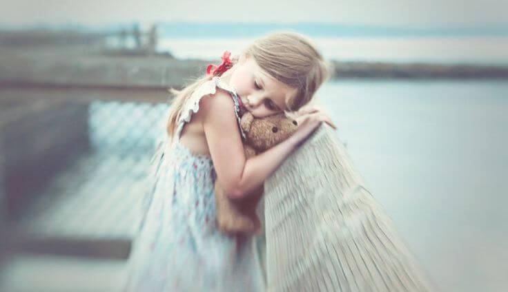 Lillepiger med mærker fra barndommen krammer bamse