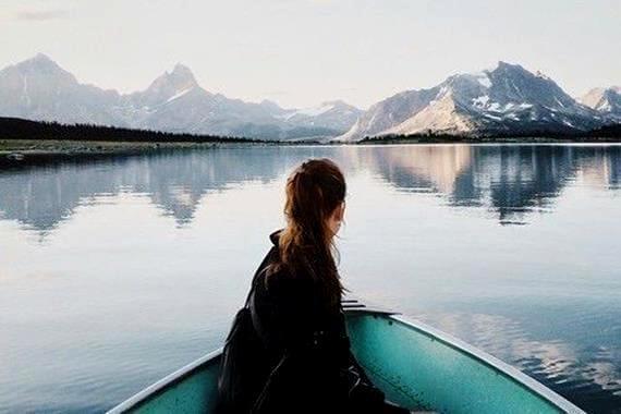 Pige på båd foran bjerge