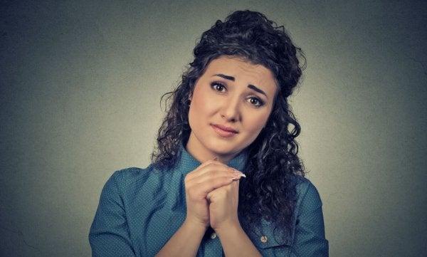 Kvinde med hænderne knuget vil bed eom ting med et blik