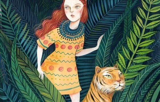Rødhåret kvinde med tiger i jungle