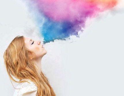 Kvinde puster farvet røg op i luften