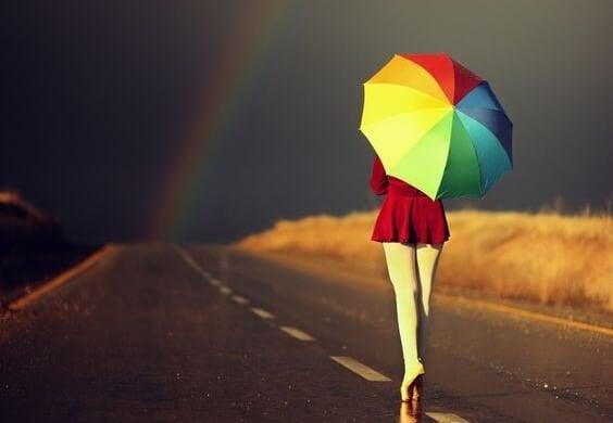 Kvinde med paraply går mod regnbue