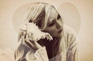 Kvinde sidder med konklylie og lytter, som hvis hun lyttede til sin krop for at tilfredsstille behov