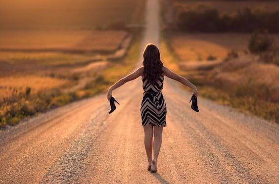 Kvinde går alene på vej med sko i hænderne