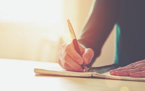 Personer skriver i notesbog